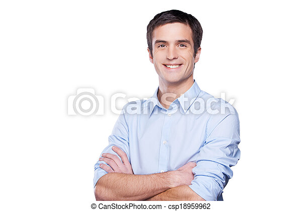 Confident businessman. Portrait of handsome young man in blue shirt looking at camera and keeping arms crossed while standing isolated on white - csp18959962
