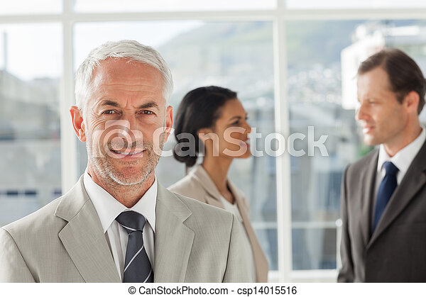 Confident businessman standing in front of colleagues speaking together in their office - csp14015516