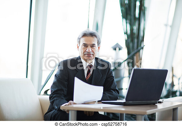 Confident businessman with documents on a laptop - csp52758716