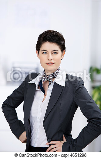 Confident Businesswoman With Hands On Waist In Office - csp14651298