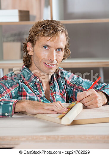 Confident Carpenter Measuring Wooden Plank At Table - csp24782229