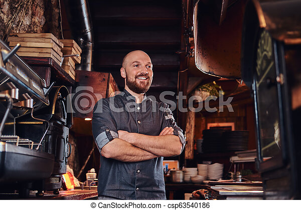 Confident chef posing with his arms crossed and looking away in a restaurant kitchen. - csp63540186