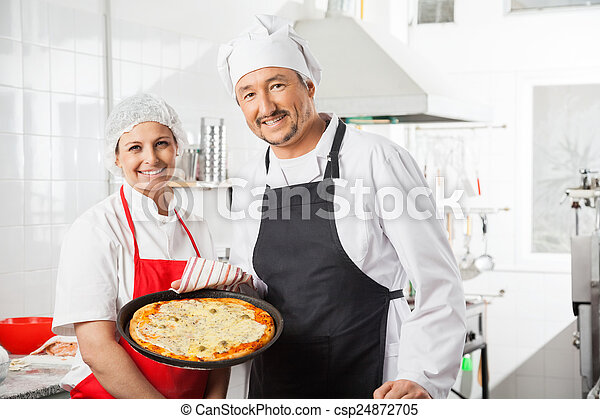 Confident Chefs With Pizza Pan At Commercial Kitchen - csp24872705