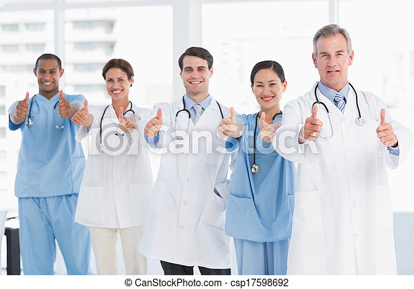 Confident doctors gesturing thumbs up at hospital - csp17598692