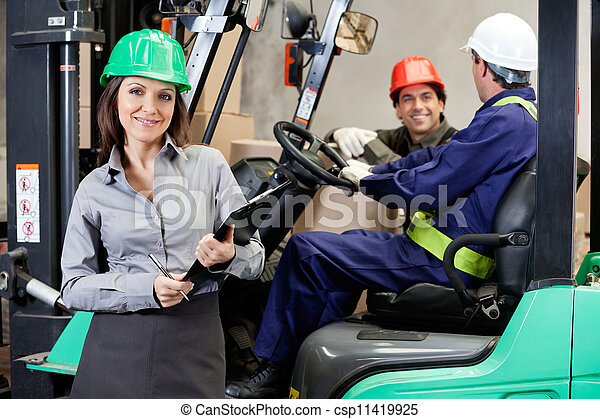 Confident Female Supervisor With Forklift Driver At Warehouse - csp11419925