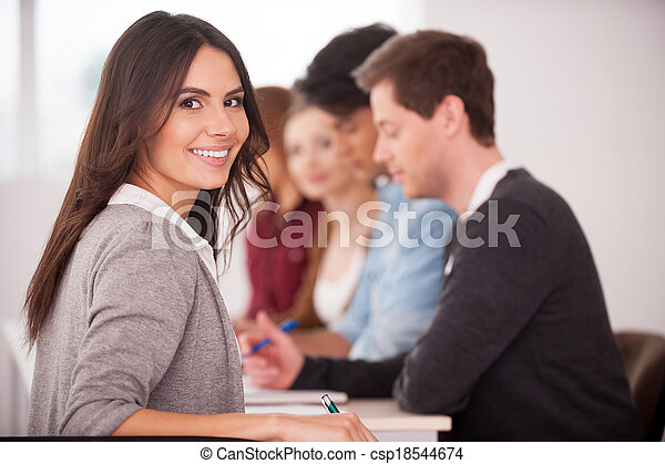 Confident in her team. Rear view of beautiful young woman looking over shoulder and smiling while sitting together at the table with another people  - csp18544674