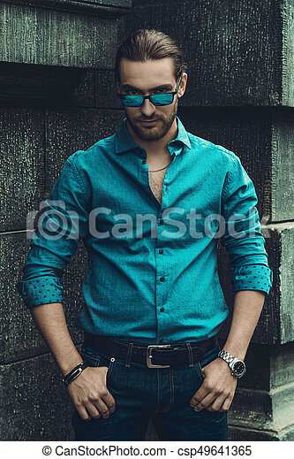 15f4bff3 Confident male look. Handsome young man in jeans clothes stands on a ...