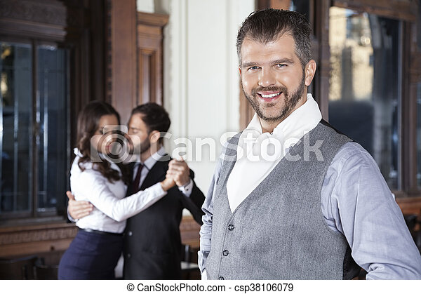 Confident Man Smiling While Dancers Performing Tango In Restaura - csp38106079