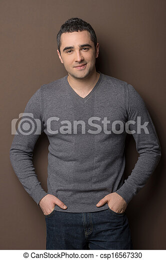 Confident mature man. Cheerful middle-aged man standing with his hands in pockets and smiling at camera - csp16567330