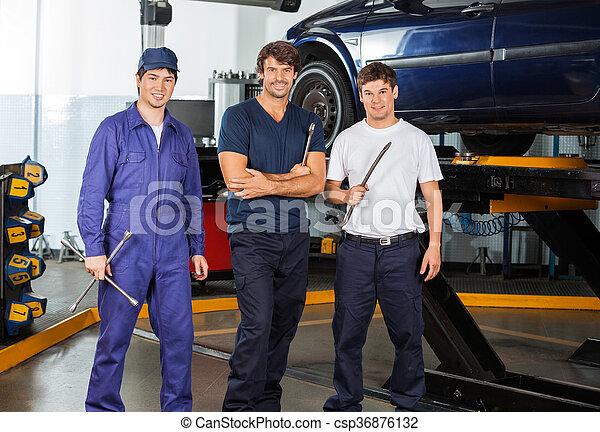 Confident Mechanics Holding Worktools At Garage - csp36876132