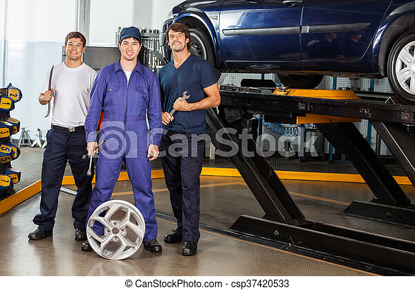 Confident Mechanics Holding Wrenches At Garage - csp37420533