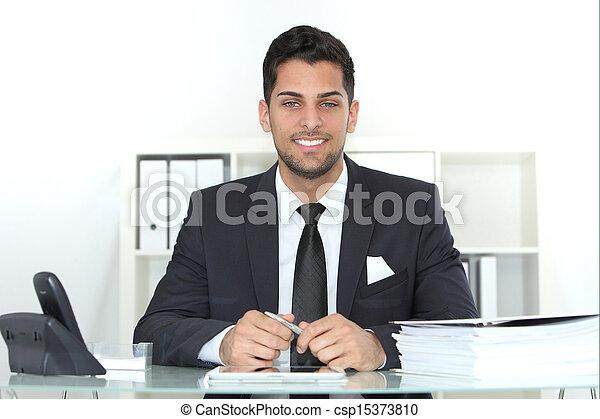 Confident successful businessman at his desk - csp15373810