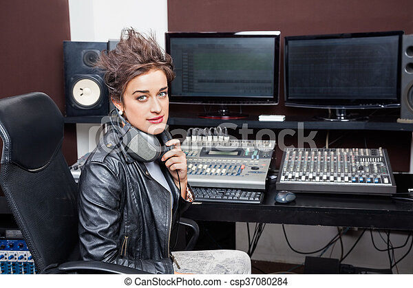 Confident Young Woman Sitting At Mixing Desk - csp37080284