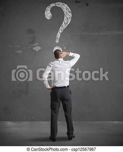 Confused businessman looking at question mark - csp12567987