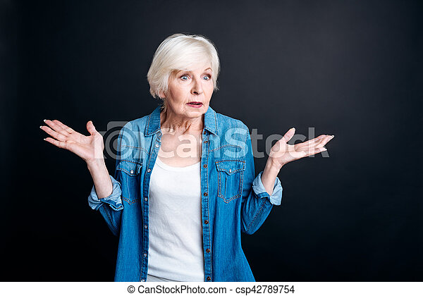 Confused elderly woman standing on black background - csp42789754
