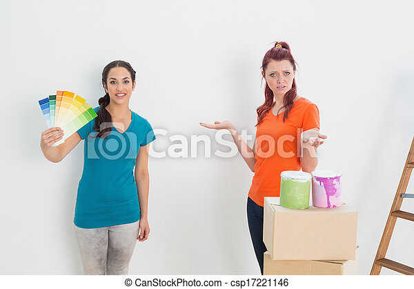 Confused friends choosing color for painting a room - csp17221146