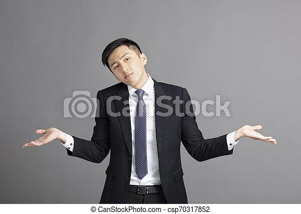 confused young businessman shrugging shoulders - csp70317852