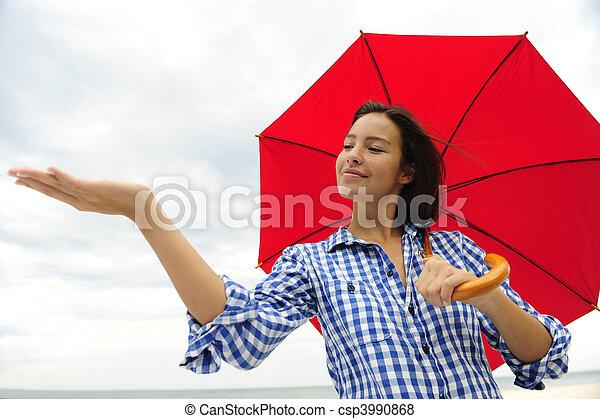 Mujer con paraguas rojo tocando la lluvia - csp3990868