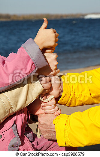 Connected hands of adults and child as symbol of unity of family. Thumb is lifted upwards! - csp3928579