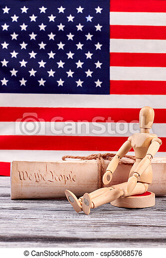 Constitution of US and wooden human dummy. - csp58068576