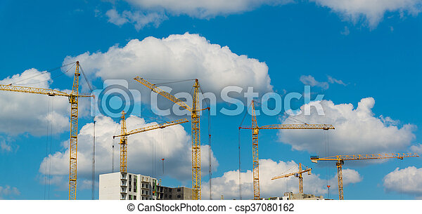 Construction cranes on background of summer sky with clouds - csp37080162