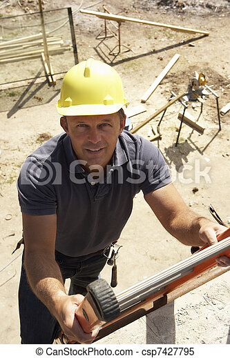 Construction Worker Climbing Ladder On Building Site For New Home - csp7427795