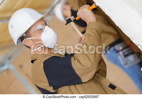 construction worker demolishing old wall with chisel and hammer - csp52503997