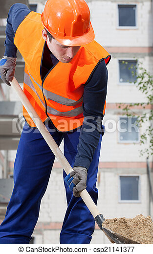 Construction worker digging sand with shovel - csp21141377