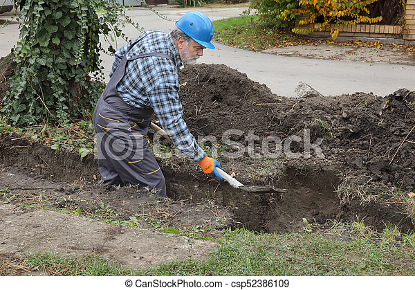 Construction worker digging trench using shovel - csp52386109