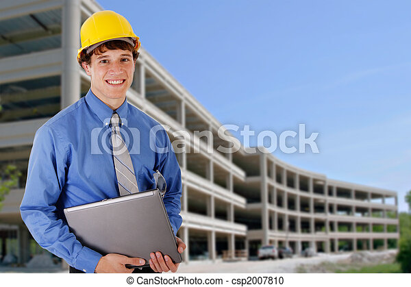 Construction Worker Holding Laptop in front of a Commercial Construction Building - csp2007810