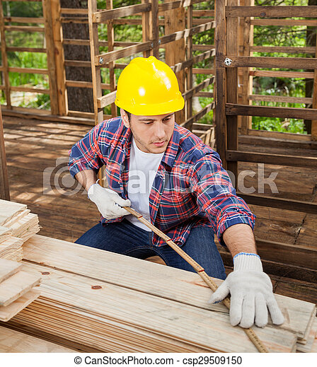 Construction Worker Measuring Wooden Plank At Site - csp29509150