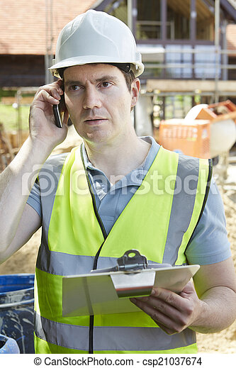 Construction Worker On Building Site Using Mobile Phone - csp21037674