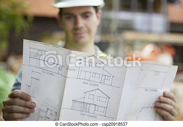 Construction Worker On Building Site Looking At House Plans - csp20918537