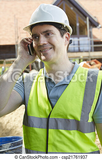 Construction Worker On Building Site Using Mobile Phone - csp21761937