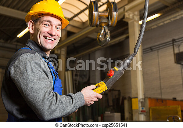 Construction worker operating crane in assembly hall - csp25651541