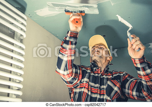 Construction Worker Patching Bathroom Ceiling - csp92042717