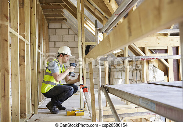 Construction Worker Using Drill On House Build - csp20580154