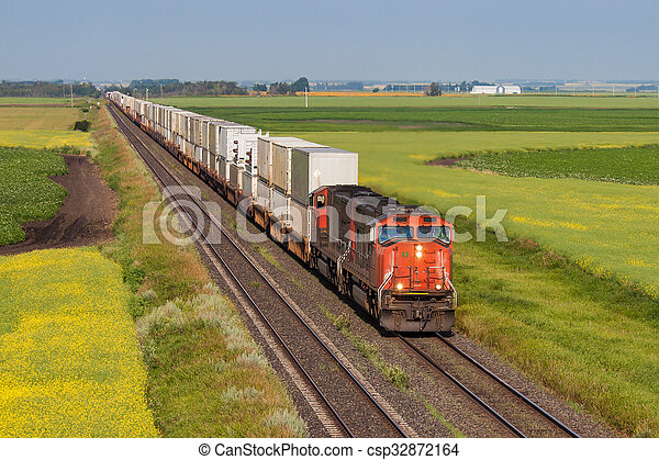Container train across green and yellow prairie - csp32872164