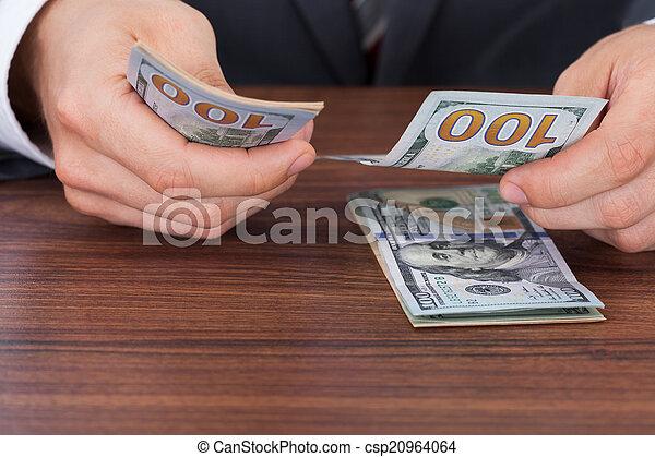 Hombre de negocios contando billetes de cien dólares en el escritorio - csp20964064