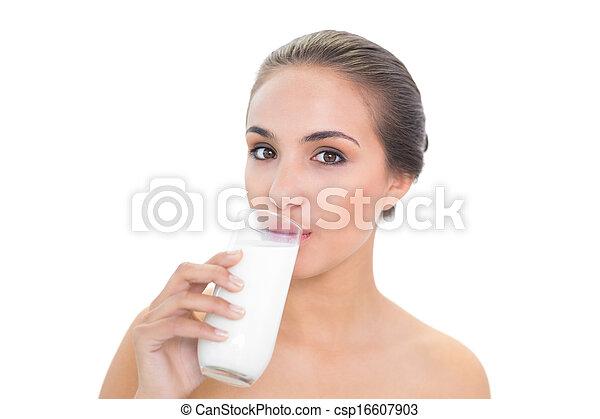 Content brunette woman drinking a glass of milk - csp16607903