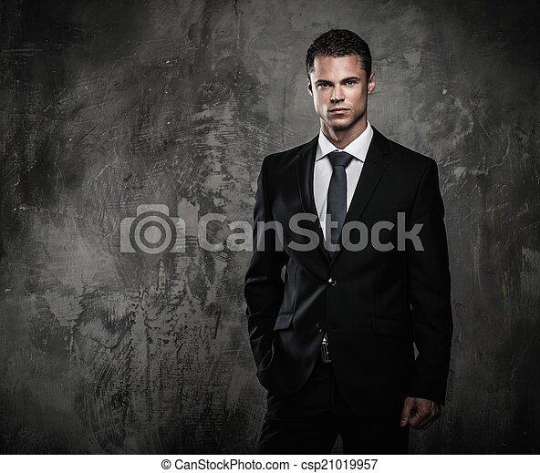 Hombre bien vestido con traje negro contra pared grunge - csp21019957