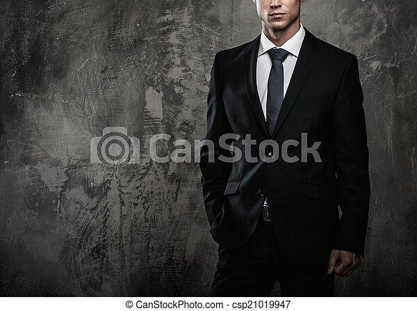 Hombre bien vestido con traje negro contra pared grunge - csp21019947