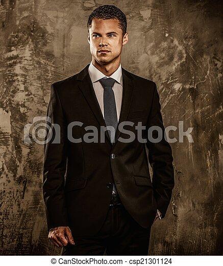 Hombre bien vestido con traje negro contra pared grunge - csp21301124