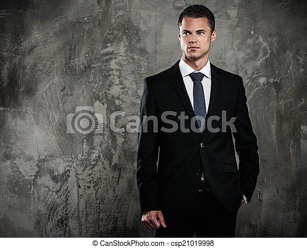 Hombre bien vestido con traje negro contra pared grunge - csp21019998