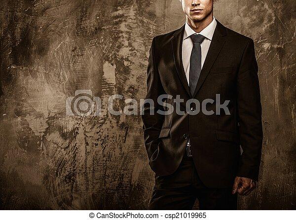Hombre bien vestido con traje negro contra pared grunge - csp21019965