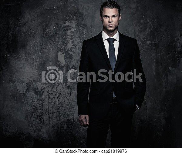 Hombre bien vestido con traje negro contra pared grunge - csp21019976