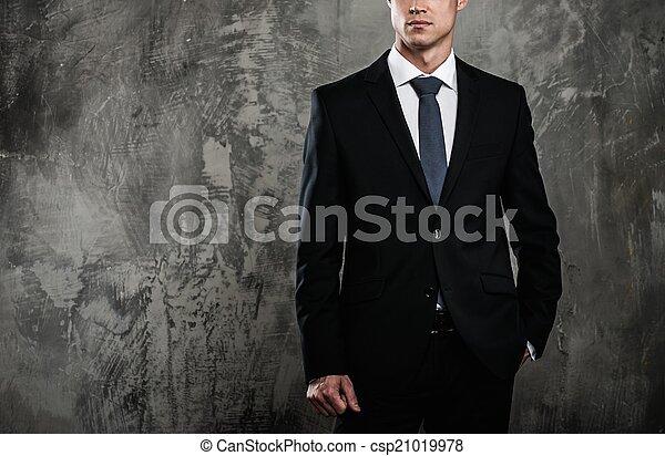 Hombre bien vestido con traje negro contra pared grunge - csp21019978