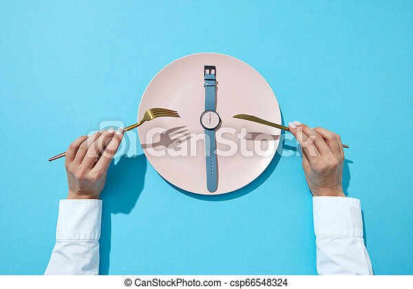 Reloj de muñeca con seis en punto y mano de mujer con tenedor y tejido en un fondo azul. Hora de perder peso, de comer control o de dieta. Planta. - csp66548324