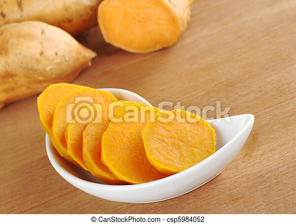 Cooked sweet potato (lat. Ipomoea batatas) cut in slices in white bowl on wooden surface with sweet potatoes in the background (Selective Focus, Focus on the sweet potato in the bowl)  - csp5984052