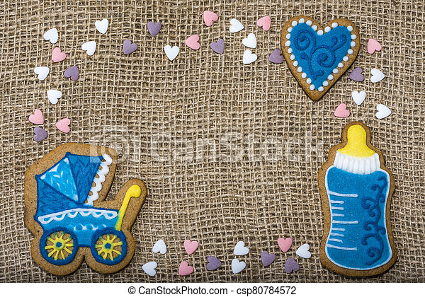 Cookies on a burlap in the form of a stroller in a bottle of baby hearts. - csp80784572